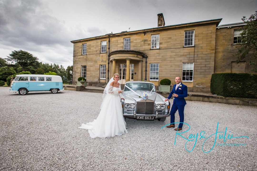 Bride and groom stood outside Saltmarshe Hall with a glass of champagne and their wedding cars