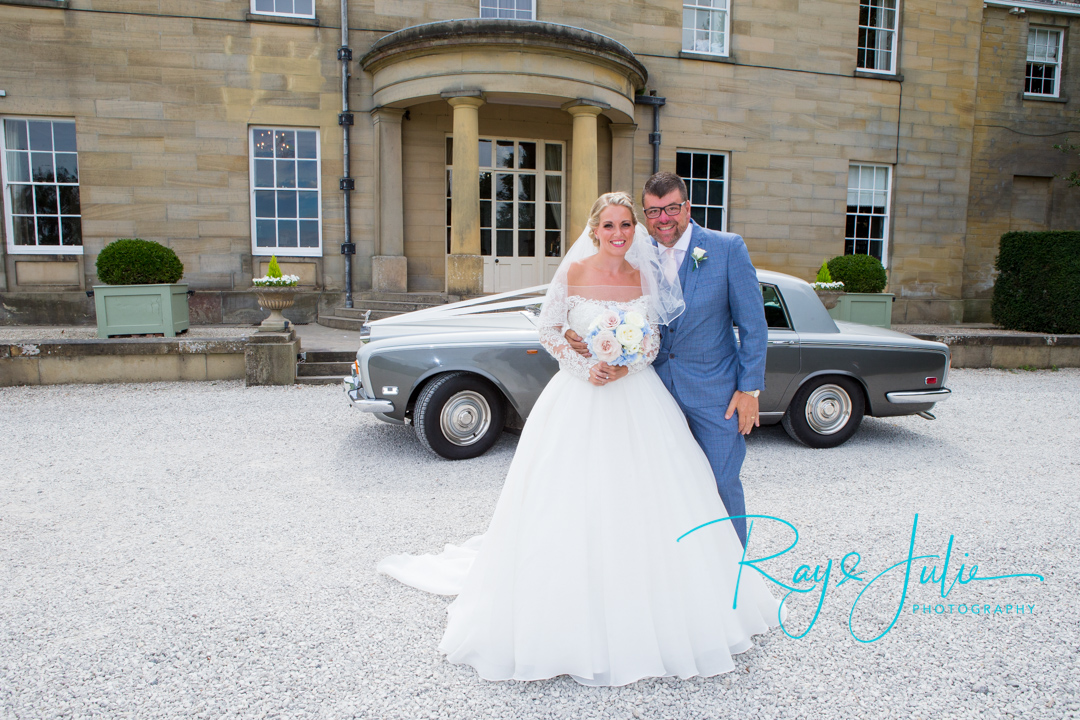 Bride with wedding flowers and dad standing outside Saltmarshe Hall. Rolls Royce bridal car in background.