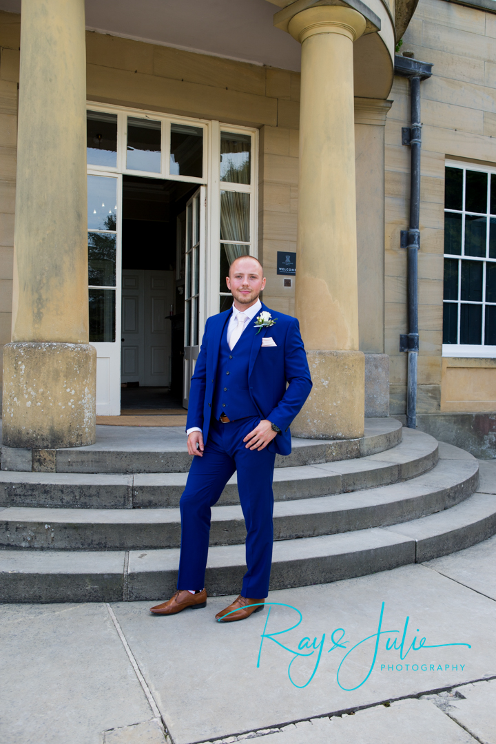 Groom stood outside Saltmarshe Hall looking very smart in a blue Slaters Menswear suit.