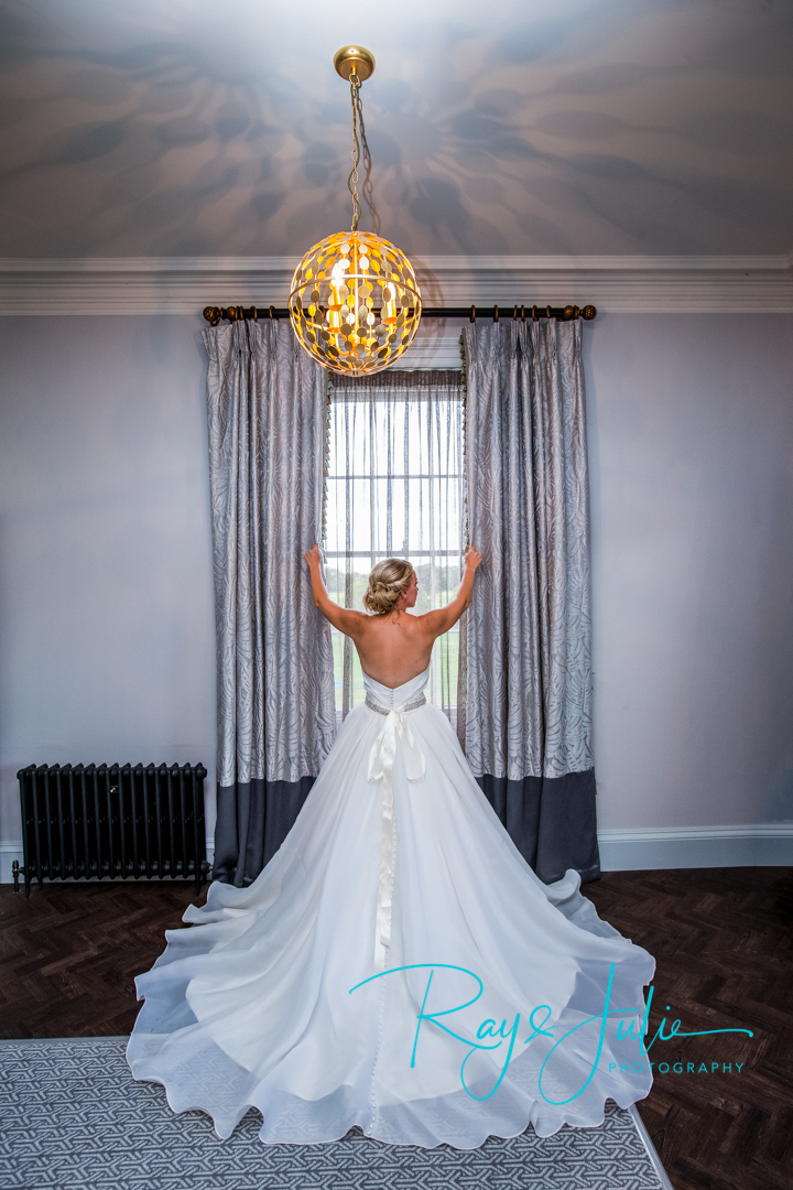 Bride stood by the window in the Yorkshire Suite at Saltmarshe Hall, in a stunning Chloe Jane wedding dress.