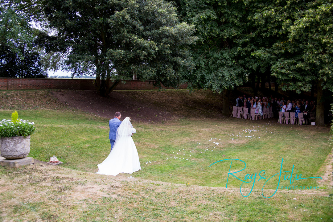 Bride and father making their way to the outside wedding ceremony area at Saltmarshe Hall, guest and groom looking at them.