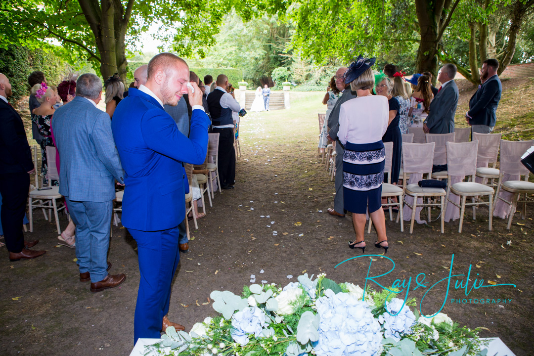 Groom crying as bride and father make their way to him, for the outdoor ceremony held at Saltmarshe Hall.