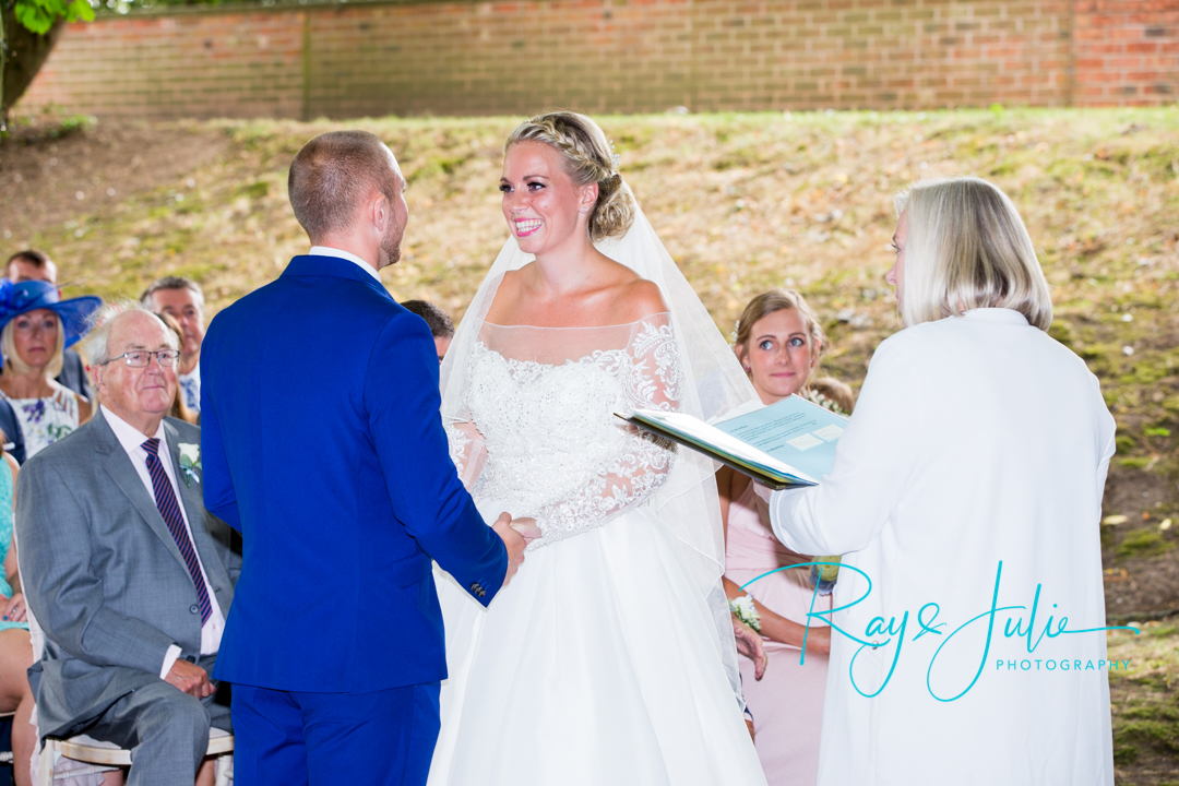 A very happy bride holding grooms hands during their outdoor ceremony at Saltmarshe Hall.