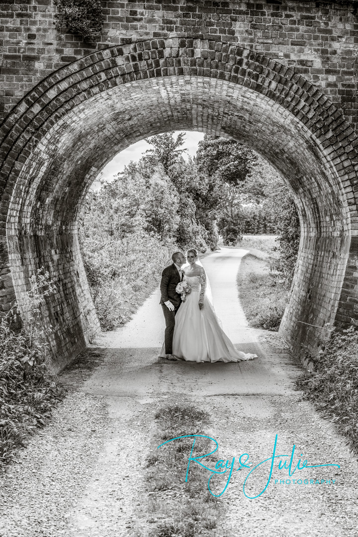 Bride and Groom under archway in Black and white. Near Saltmarshe Hall.