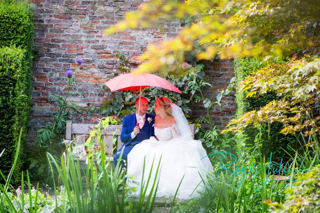Bride and groom sat on a bench taking shelter from the rain under a love heart shaped umbrella, in the stunning grounds at Saltmarshe Hall.