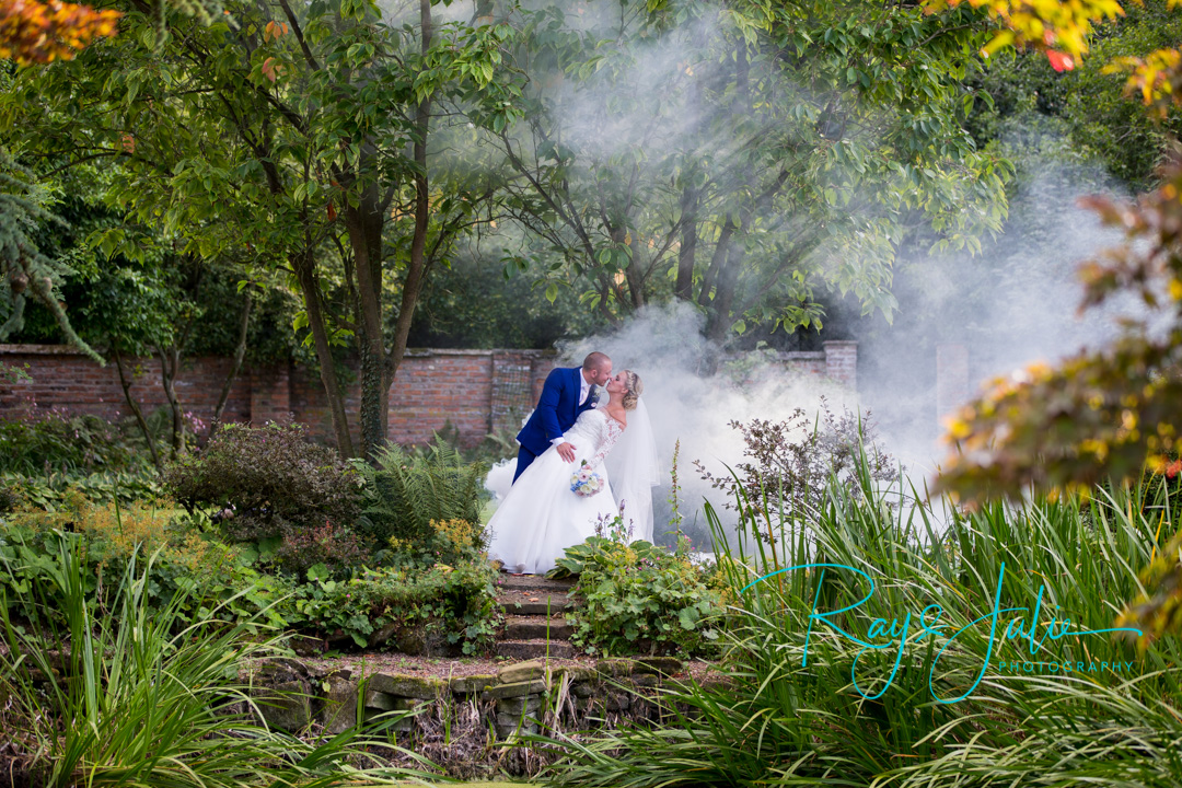 Stunning photograph of bride and groom bent over about to kiss in the grounds at Saltmarshe Hall. Smoke behind with flowers by All Occasions of Howden.