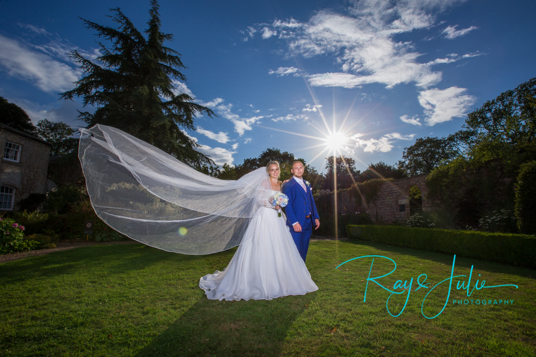 Bride with veil blowing and Groom looking very smart. With bright sunburst taken in the grounds at Saltmarshe Hall.