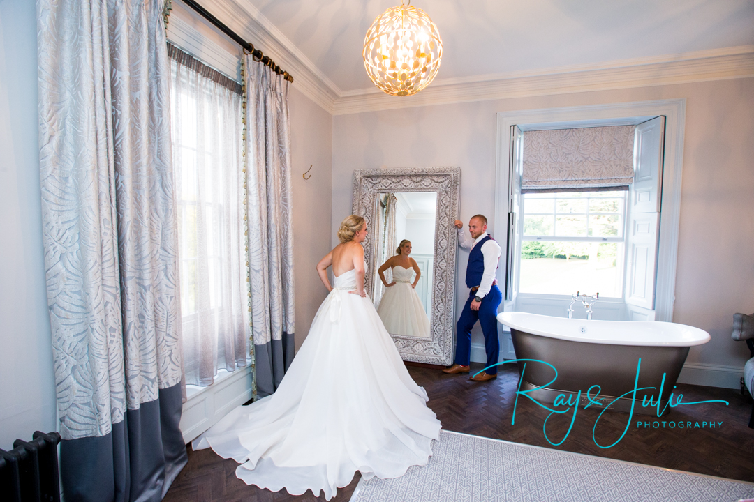 Bride showing her husband her Chloe Jane wedding dress in the Yorkshire Suite at Saltmarshe Hall.