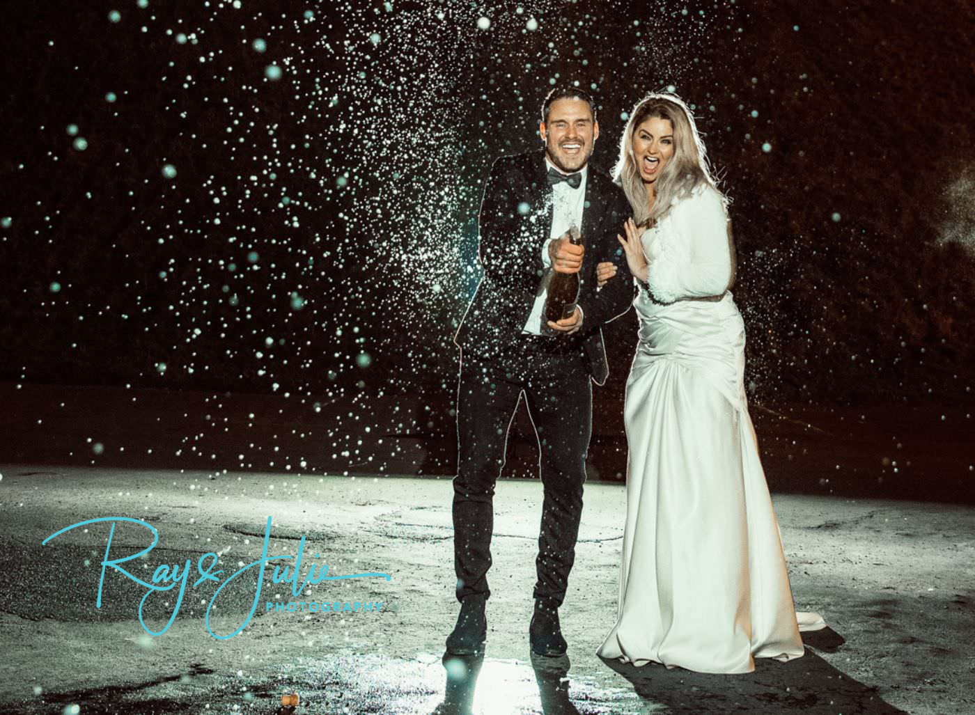 A newley married couple celebrating by popping a bottle of champagne