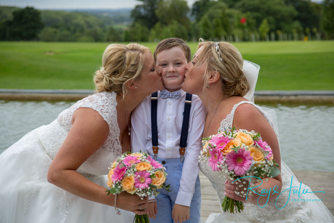 Bride and bride kissing their pageboy outside the KP Club