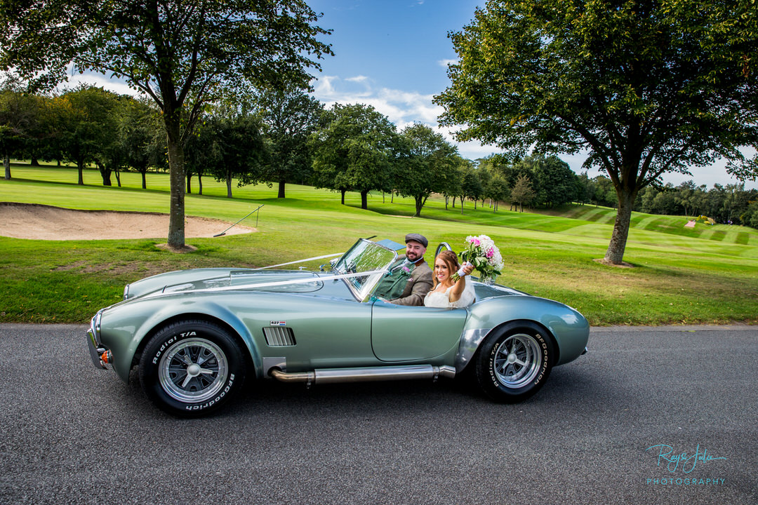 Bride and Groom driving in Shelby Cobra photographed by Ray and Julie Photography.