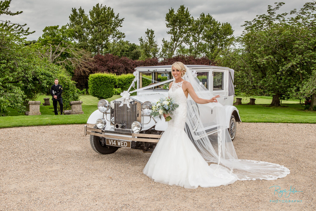 Bride and groom with vintage car outside Tickton Grange East Yorkshire.