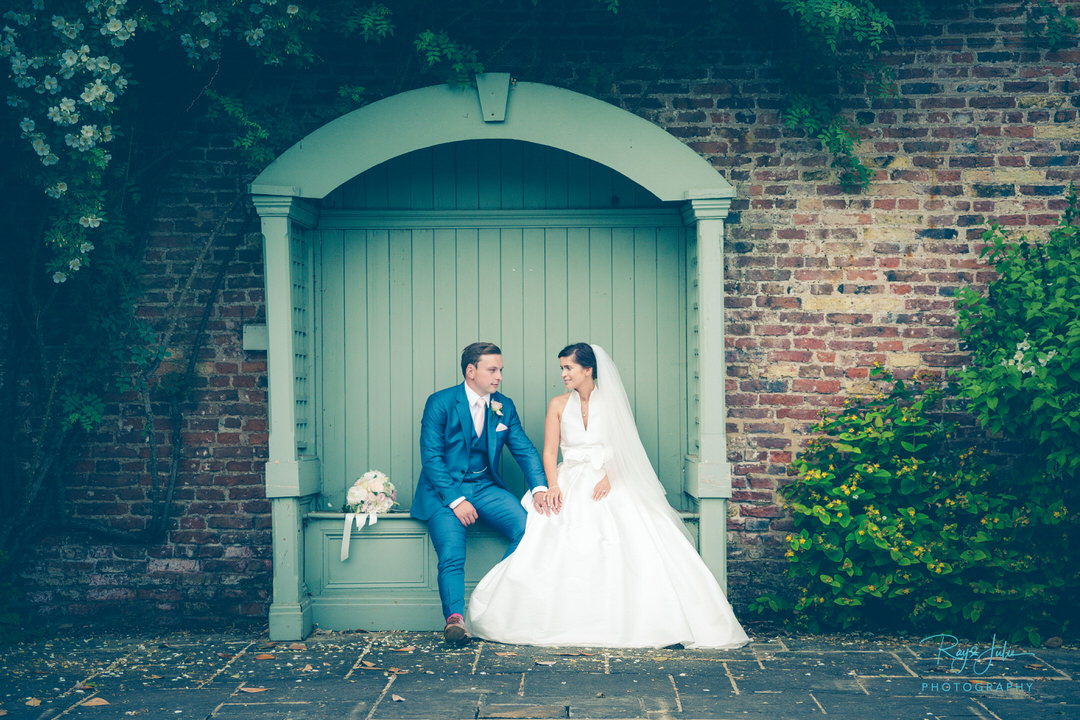 Bride and Groom outdoor sat down looking at each other wedding photograph captured at Saltmarshe Hall East Riding of Yorkshire.