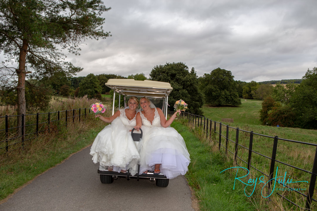 Bride and Bride smiling on the back of a golf buggy. Just after being married at the KP Club. Wedding photographs by Ray and Julie Photography