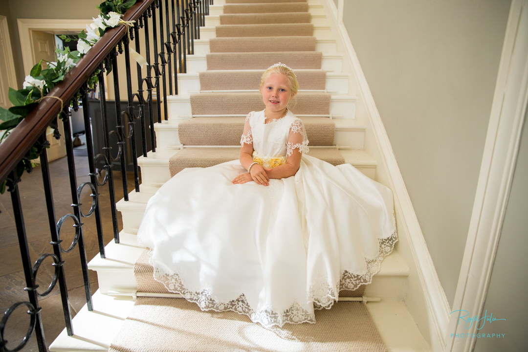 Flower girl sat on the stairs in a handmade wedding dress. Photograph Ray and Julie Photography