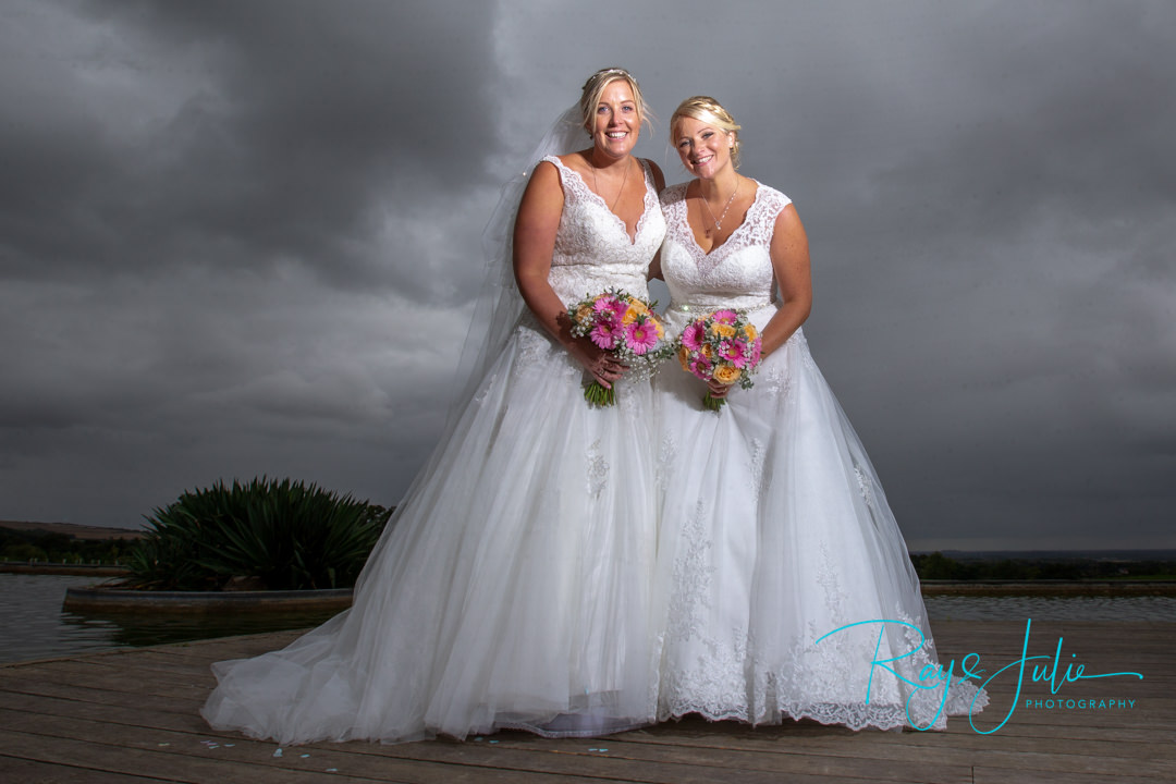 Bride and Bride, beautiful wedding photograph. Both looking stunning in their wedding dresses with a strong sky. Photography at The Kp Club by Ray and Julie Photography.