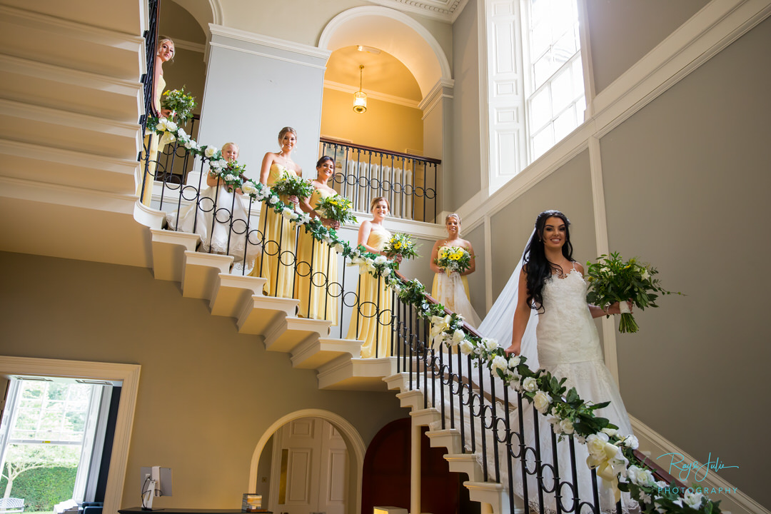 Bride and bridesmaids walking down the grand staircase at wedding venue Saltmarshe Hall East Yorkshire