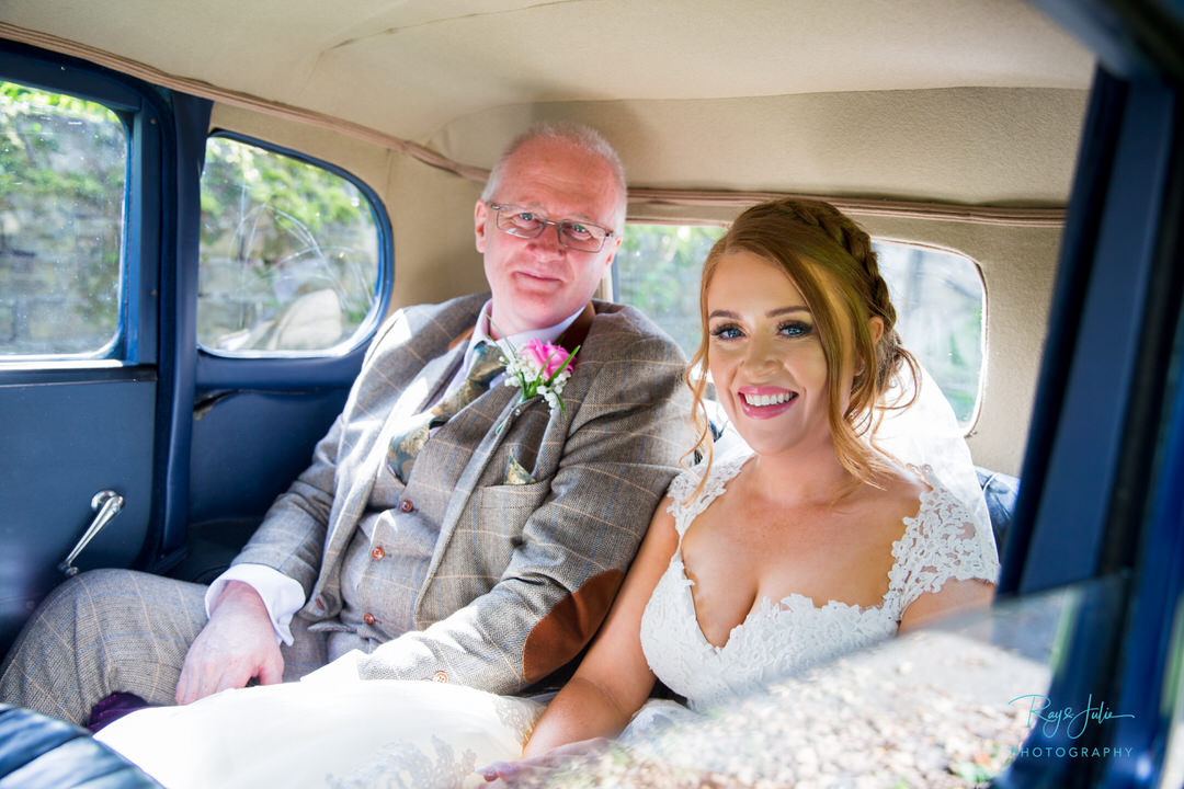 Bride and dad arriving in vintage wedding car to the church in West Yorkshire.