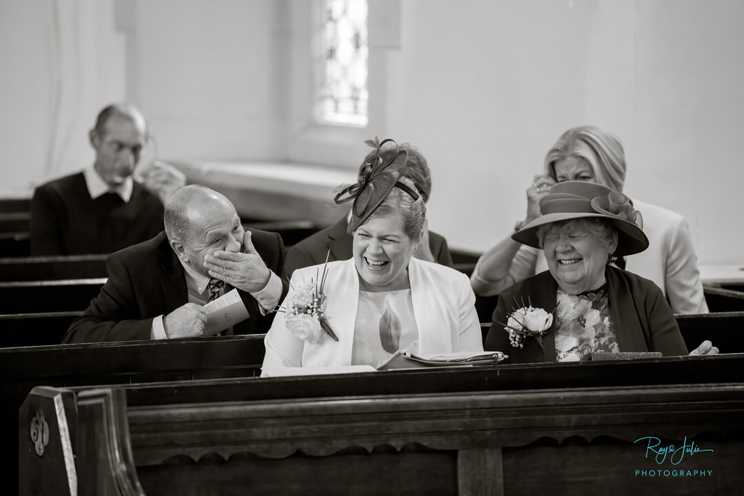 Wedding guests laughing after sharing a joke in church prior to the ceremony starting. Black and white photograph taken by Ray and Julie Photography.