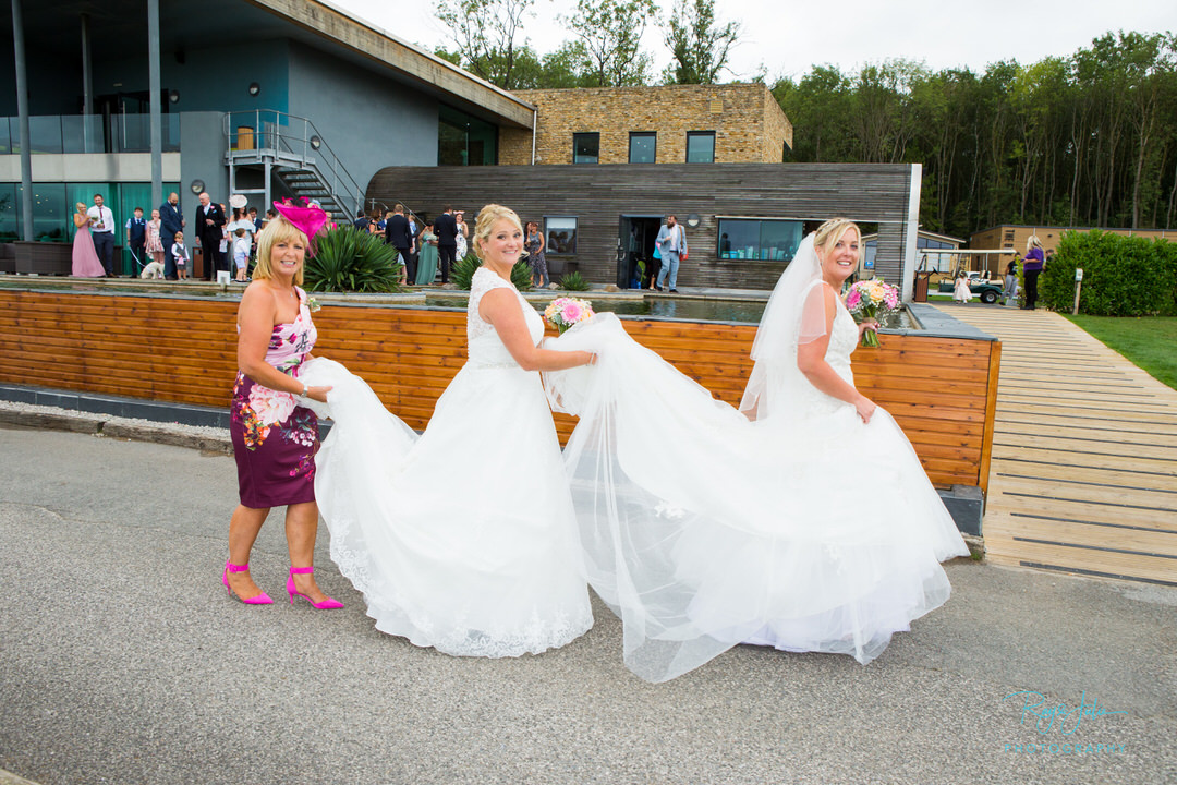 Stunning brides in wedding dresses with pretty mum carrying the wedding dress behind. photographed at The KP Club.