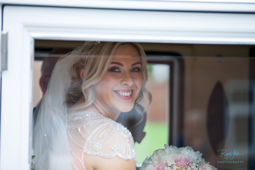 Bride arriving to the church smiling through the vintage car window.