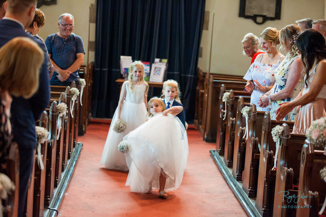 Everyone laughing at flower girl in church, as she lifts here dress very high to walk down the aisle before the bride