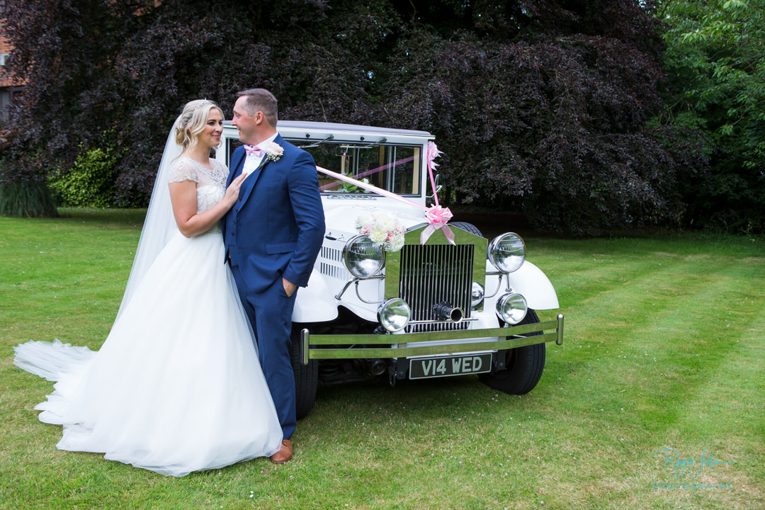 Bride and Groom looking at each other stood next to a vintage wedding car. Wedding venue Hull and East Riding of Yorkshire.