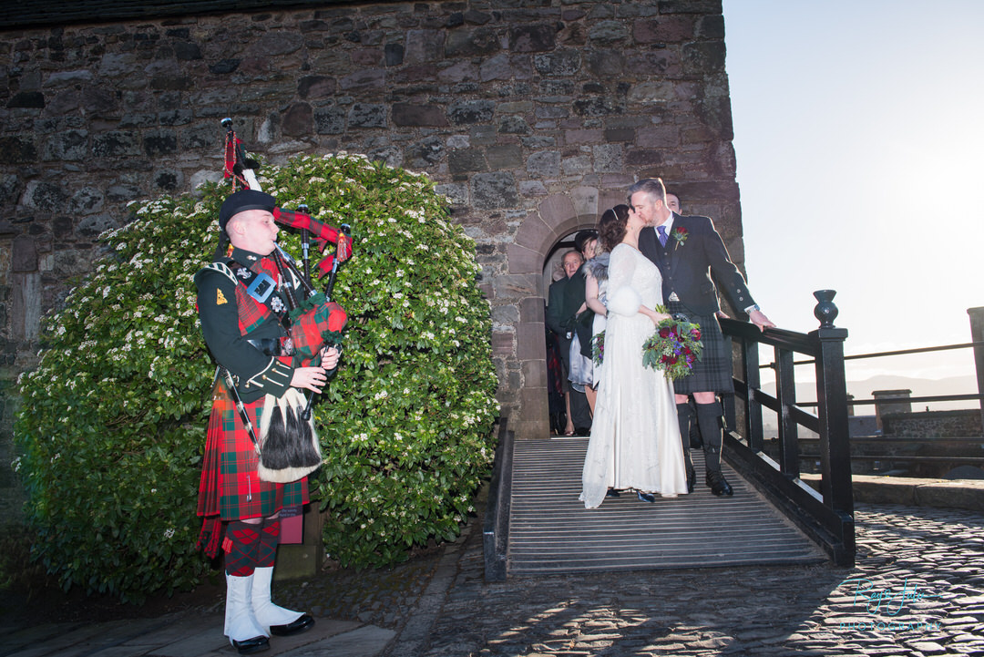 Bride and groom kissing outside of St Margaret's Chapel Edinburgh Castle, whilst piper plays. Photographed by award winning photographers Ray and Julie Photography.