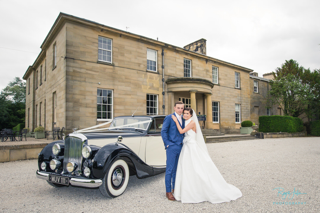 Good looking bride and groom stood outside Saltmarshe Hall East Yorkshire. Photograph taken just after their wedding ceremony with a vintage car also in the photograph.