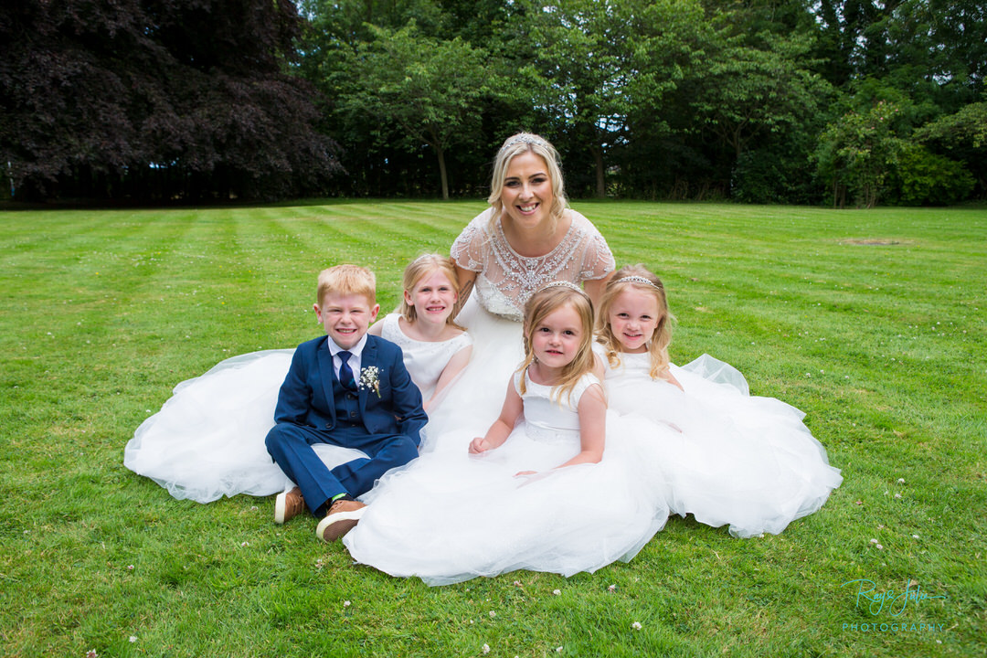 Bride with flower girls and page boy sat around her on the grass, just after being married. Venue Hull and East Yorkshire.