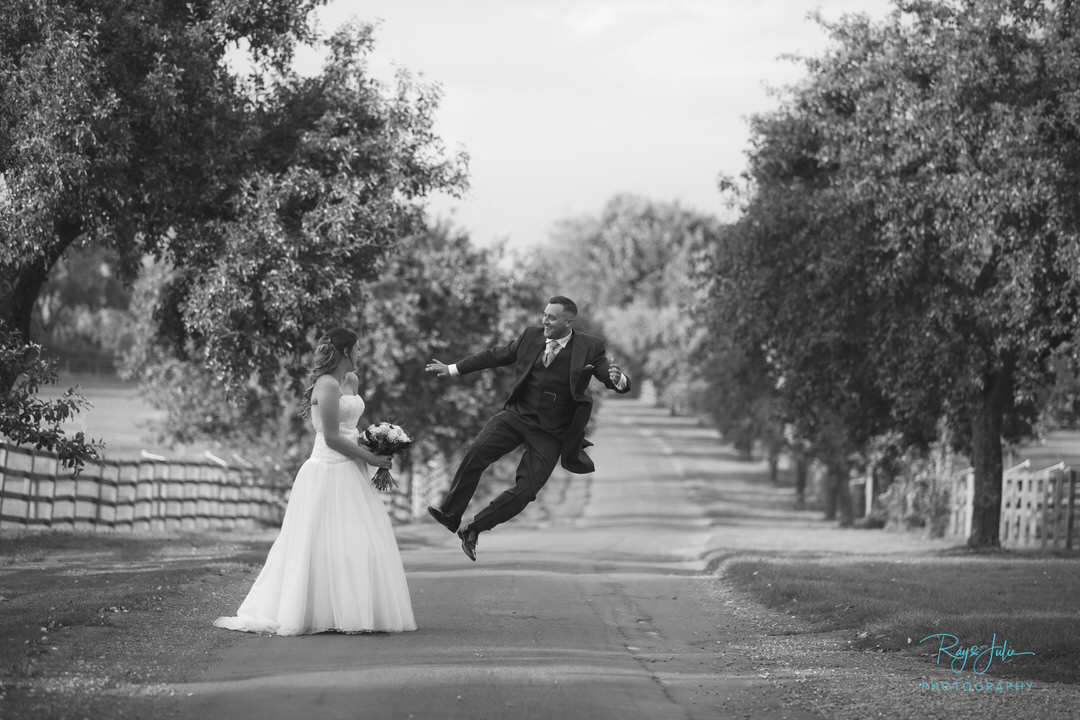 Bride and Groom at Rowley Manor. Groom kicking his heels very happy at just getting married. Photograph by award winning Ray and Julie Photography