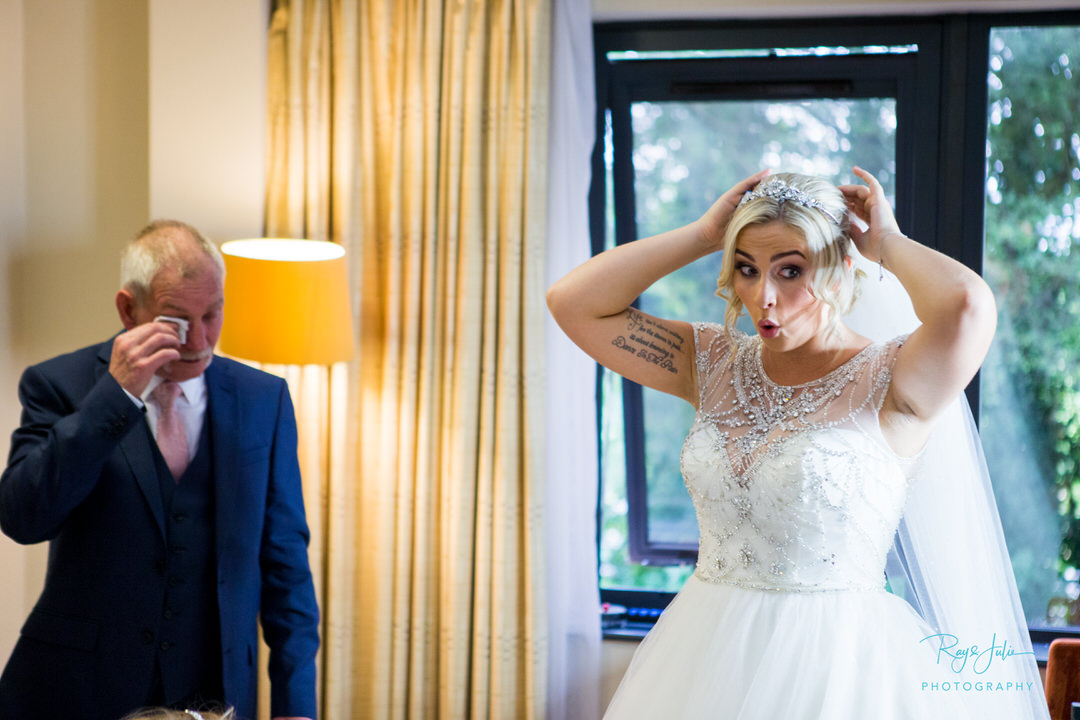 Bride trying to stop herself from crying so not to mess her make-up, as dad is crying in background after just seeing his daughter in her wedding dress for the first time.