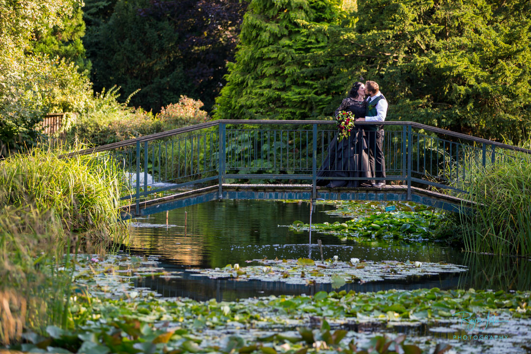 Bride in a beautiful black dress kissing her groom on the bridge at Burnby Hall East Yorkshire