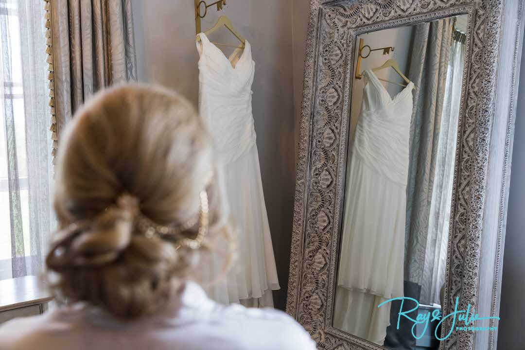 Bride looking at her dress hanging up at Saltmarshe Hall