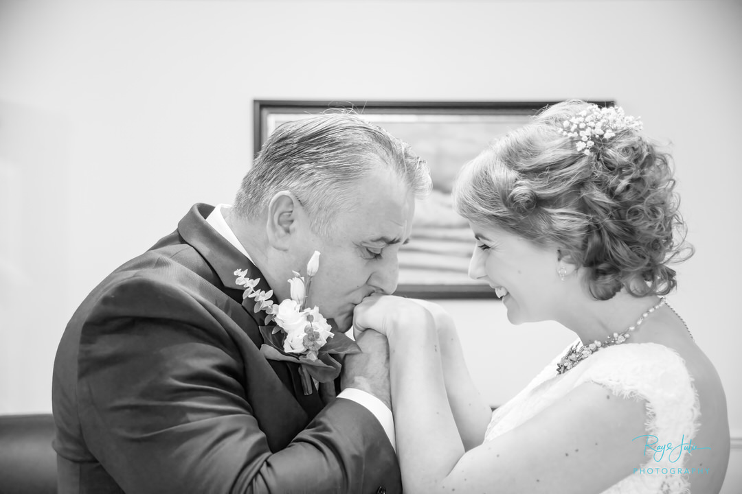 A very proud father of the bride, kissing his daughters hand. Black and white photo