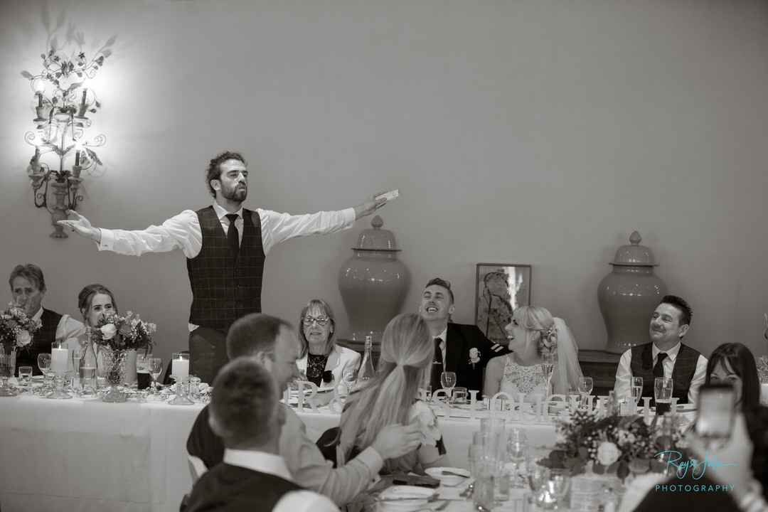 Best man taking the applause after his speech at Tickton Grange Hotel. Black and white photo