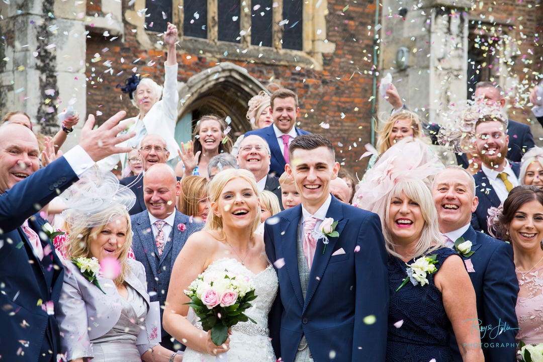 Bridal Party and wedding guests outside church throwing confetti over the bride and groom