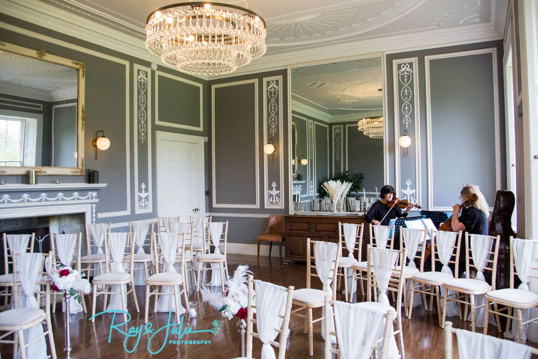 Wedding ceremony room at Saltmarshe Hall with musicians playing at the back.