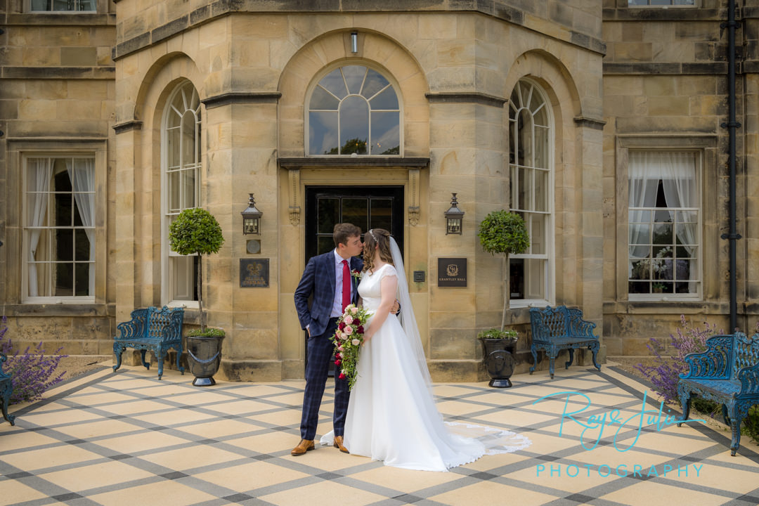 Bride and Groom kissing outside Grantley Hall main entrance
