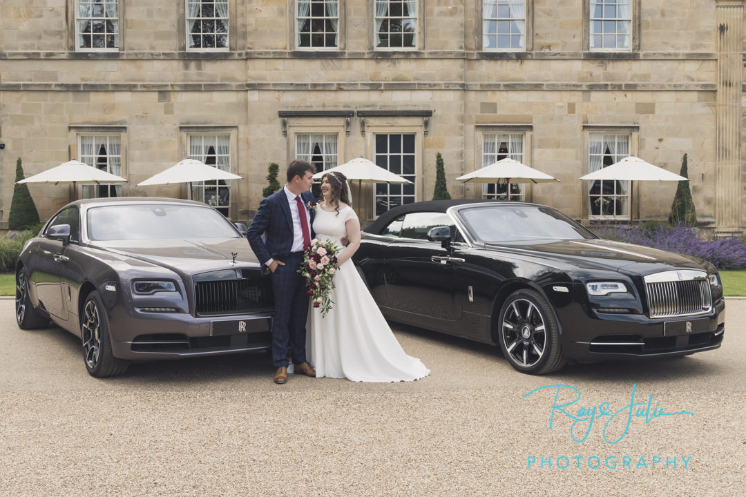 Wedding couple stood next to two Rolls Royce's outside Grantley Hall