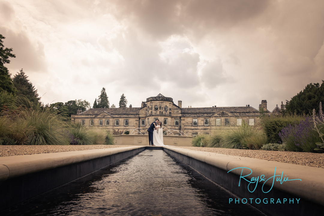 Wedding couple embrace Grantley Hall and water fountain behind them
