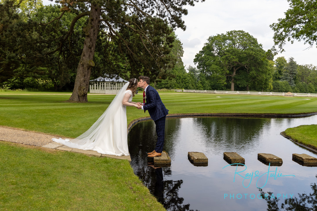 Wedding couple kissing on stepping stones at Grantley Hall