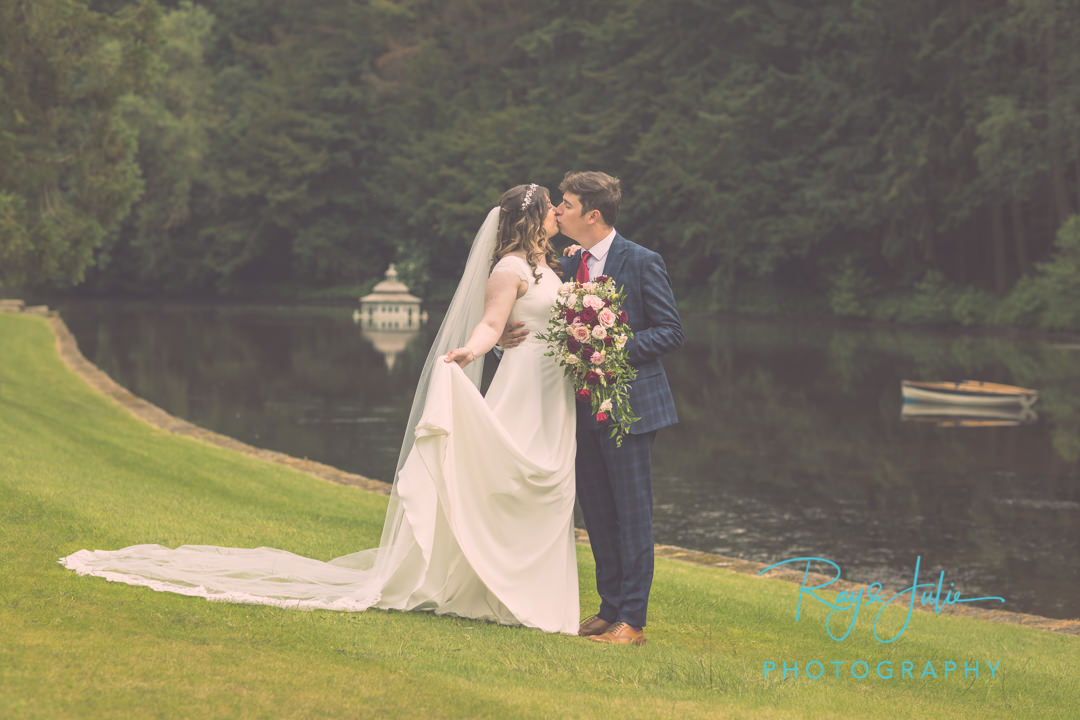 Wedding couple kissing in the grounds at Grantley Hall