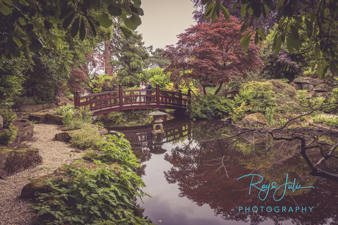 Bride and groom on bridge in the Japanese garden at Grantley Hall