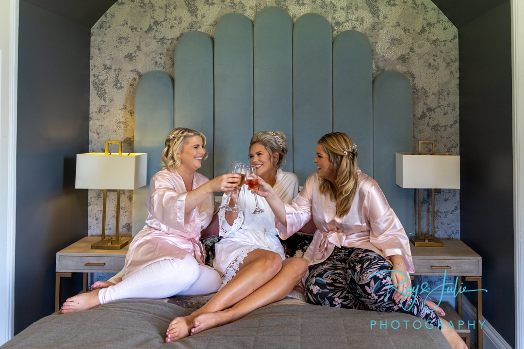 Bride and Bridesmaids with a glass of champaign on the bed in the Yorkshire Suite at Saltmarshe Hall