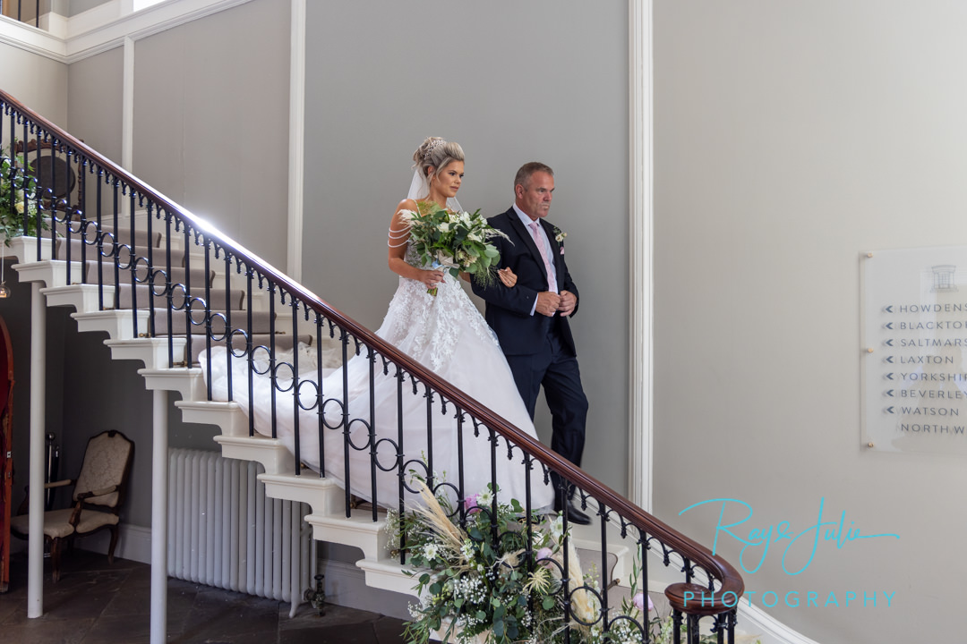 Bride and Father coming down the stairs at Saltmarshe Hall going to the wedding ceremony.