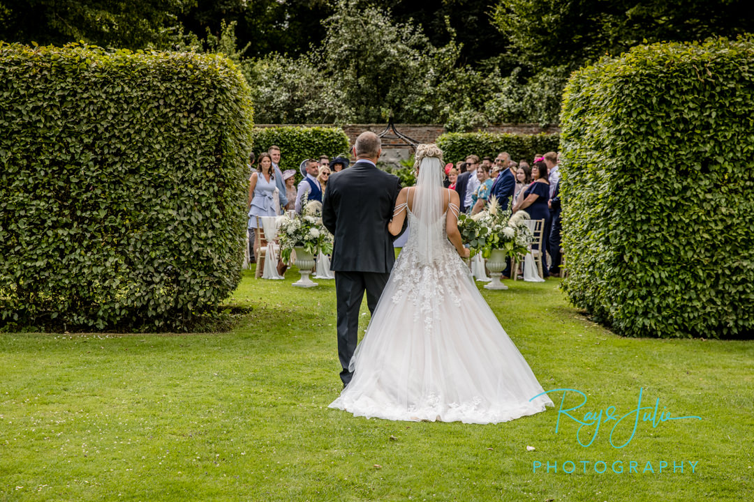 Bride and Father walking to groom at an outdoor wedding ceremony in Saltmarshe Hall's Walled Garden