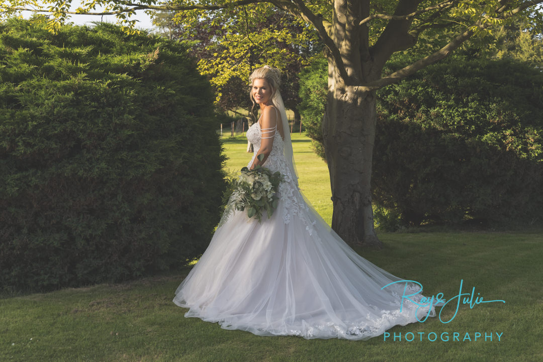 Stunning bride in beautiful wedding dress from Jane's Bridal Wear in the grounds at Saltmarshe Hall