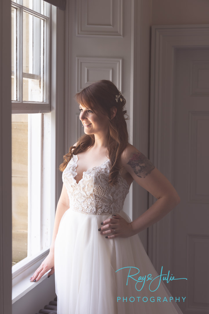 Stunning bride in wedding dress smiling looking out a window