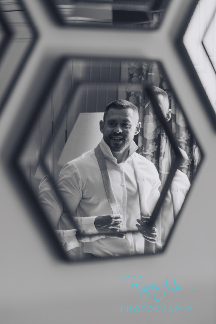 Groom reflection in a mirror putting on his tie.